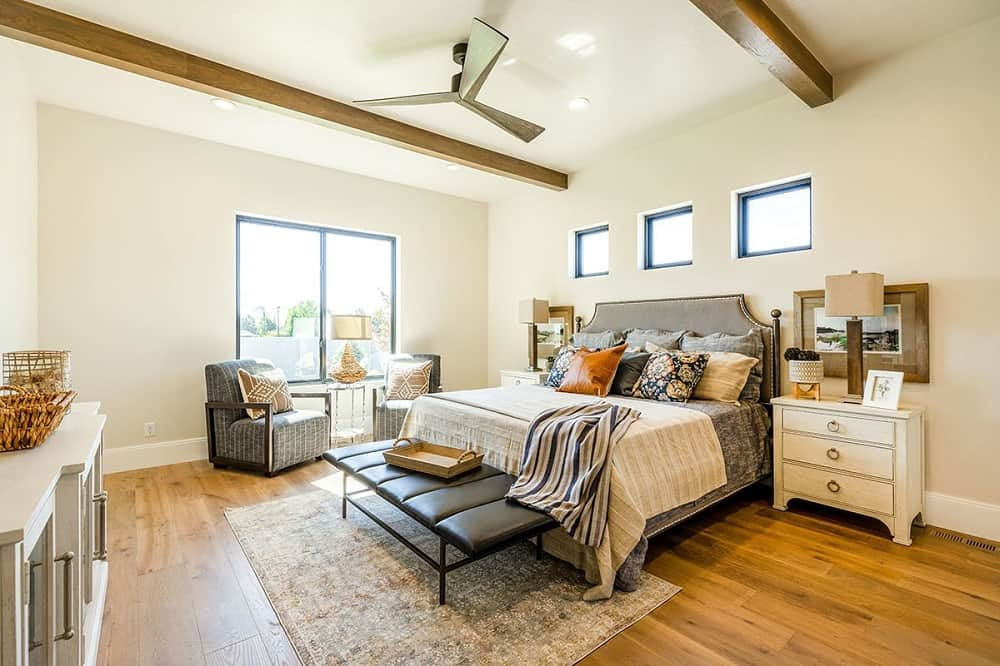 This is the primary bedroom with a large gray cushioned bed flanked by beige bedside drawers that match the walls and ceiling that has a couple of exposed beams.