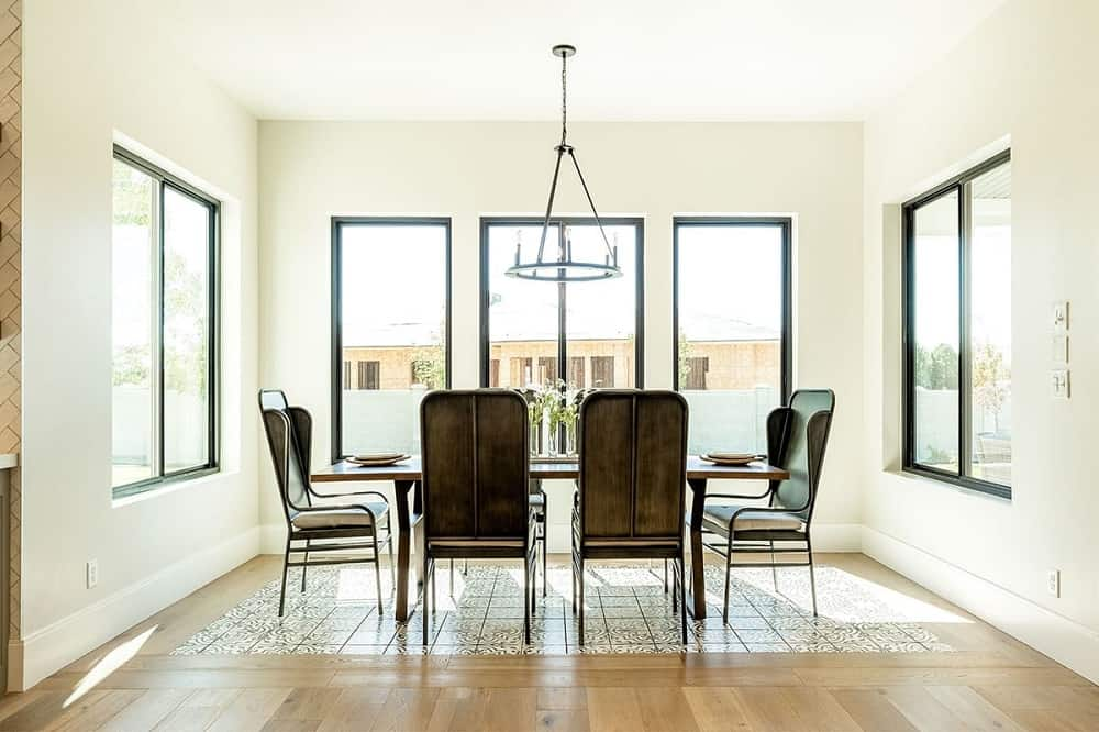 This is a close look at the dining room with large glass windows surrounding the wooden rectangular dining table paired with wrought-iron chairs and topped with a round chandelier.