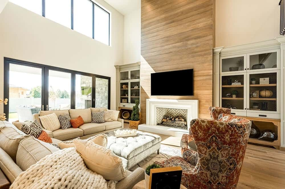This is a close look at the living room that has a couple of beige sofas and a couple of cushioned chairs with a tufted square ottoman across from the fireplace and TV mounted on the wooden shiplap wall.