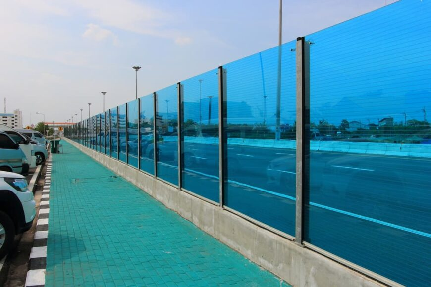 This is a close look at a highway with sound barriers lining the side made of soundproof glass.