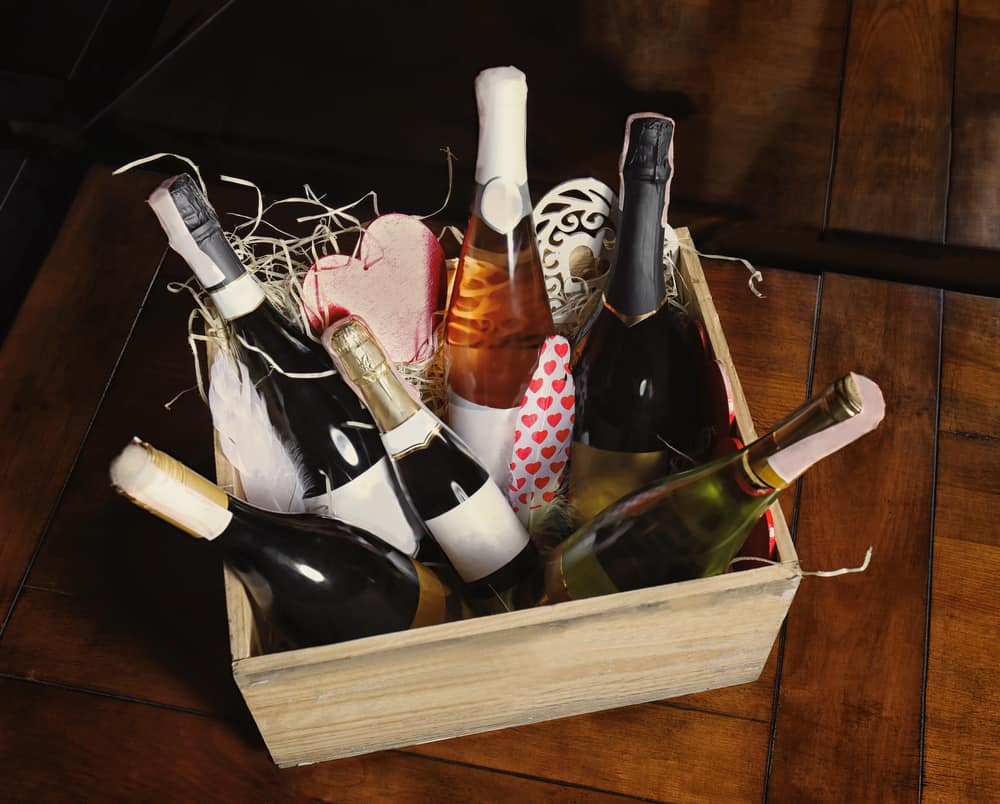 A rustic crate with multiple bottles of wine inside in different sizes.