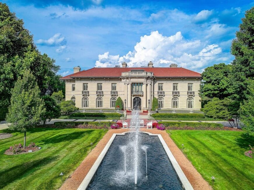 This is an aerial view of the front of the house that has a large fountain water feature surrounded by grass lawn s atall trees that pair well with the beige exterior walls topped with red tile roof. Image courtesy of Toptenrealestatedeals.com.