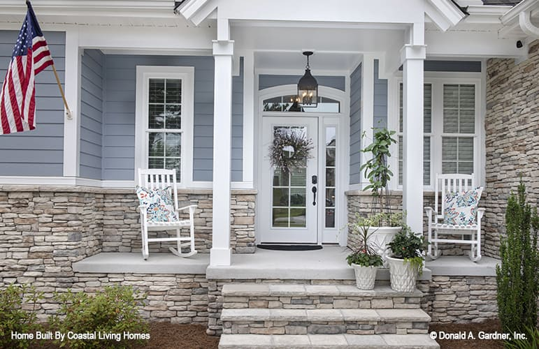 Covered front porch with stone accents, white columns, and matching rockers accentuated with floral pillows.