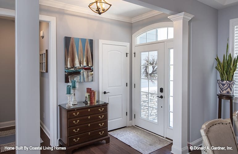 A glazed entry door opens into the foyer with a wooden dresser and a small rug that lays on the hardwood flooring.