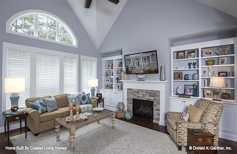 Great room with a vaulted ceiling, beige seats, white built-ins, and a stone fireplace topped with a TV.