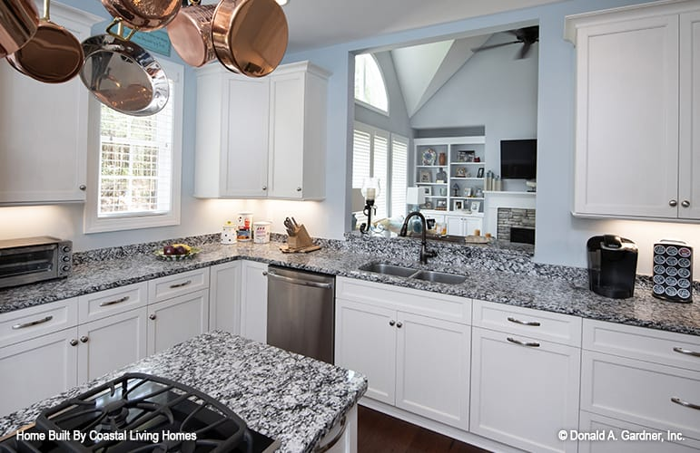 The kitchen is equipped with a double bowl sink, granite countertops, white cabinetry, and a hanging pot rack suspended over the cooktop island.