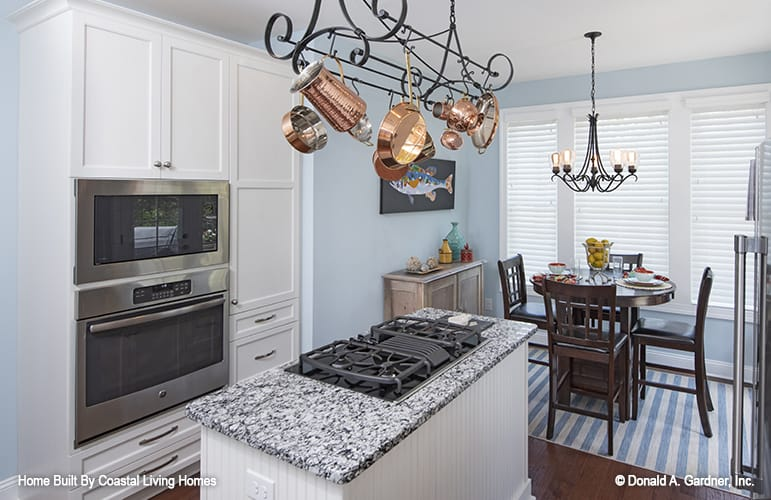 The kitchen includes an adjoining breakfast room with a round dining set over a striped area rug.
