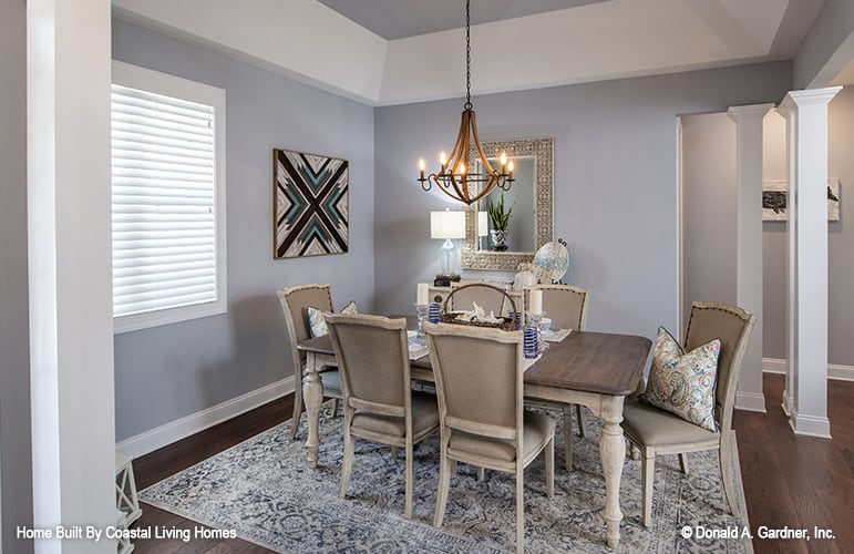 The dining room has a rectangular dining set, a warm chandelier, and gray walls adorned with a decorative mirror and artwork.