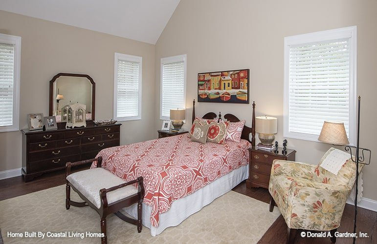 Primary bedroom with a vaulted ceiling, a comfy bed, cushioned seats, and a dark wood vanity.
