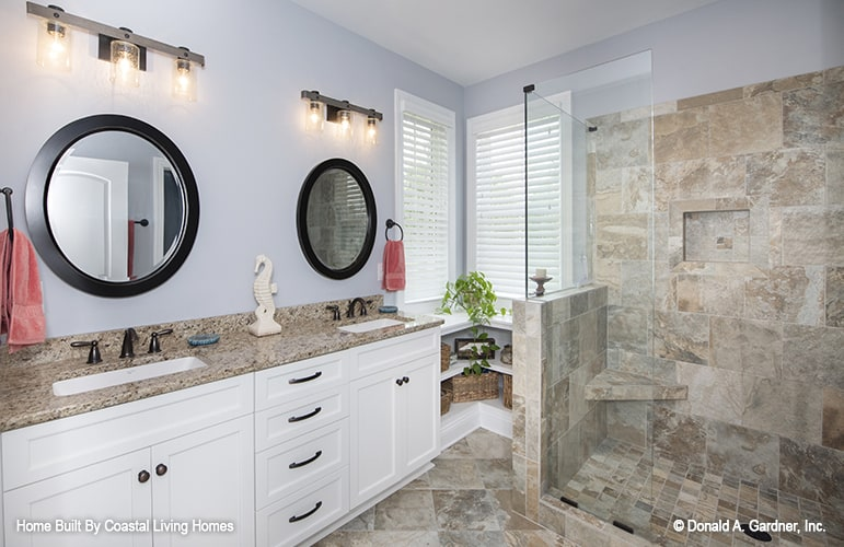 The primary bathroom has a walk-in shower and a dual sink vanity paired with round mirrors.