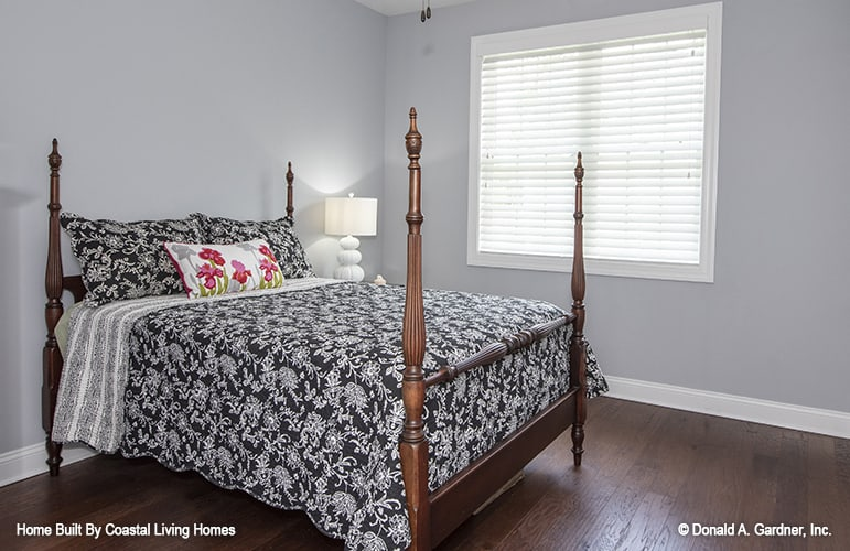 This bedroom features a four-poster bed that blends in with the hardwood flooring.