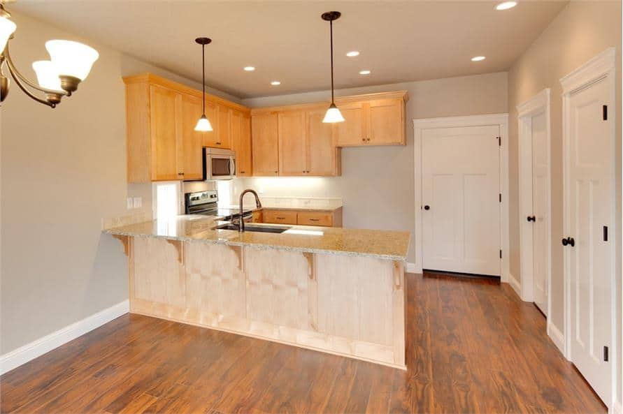 Kitchen with light wood cabinets, a breakfast bar, and walk-in pantry concealed behind the white door.