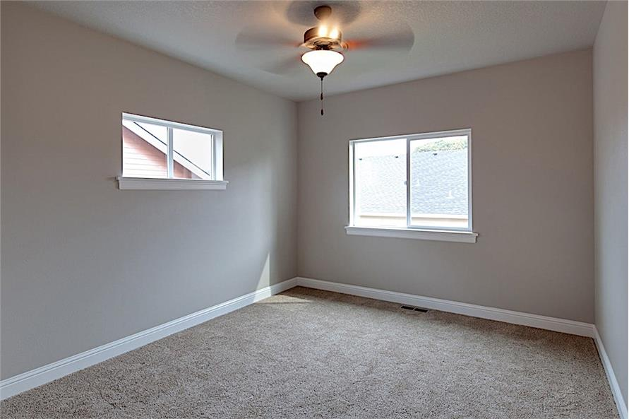 Primary bedroom with beige walls, carpet flooring, and sliding windows that invite natural light in.