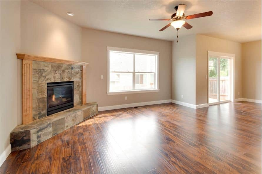 The living room has hardwood flooring, a stone fireplace, and a regular ceiling mounted with a fan.