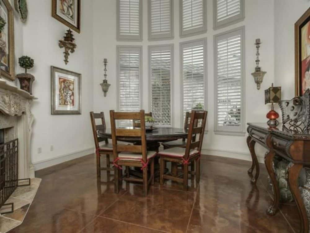 Formal dining room with a bow window, a corner fireplace, and a round dining set.