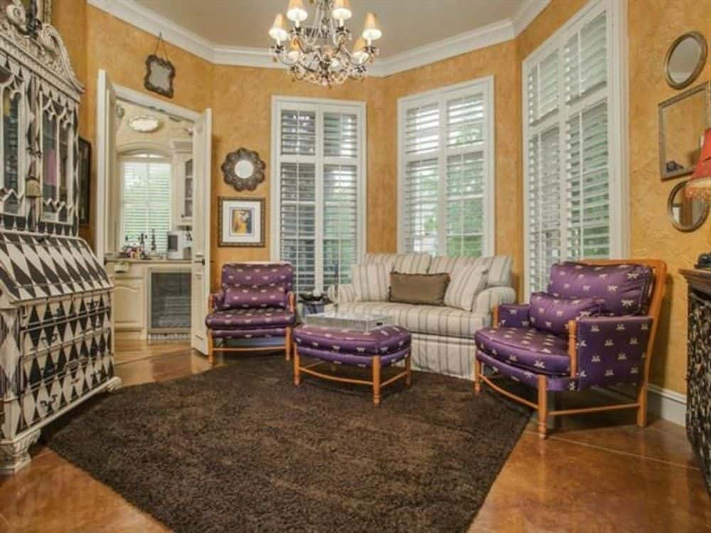 Living room with a bay window, a striped sofa, purple patterned chairs, and a matching ottoman.