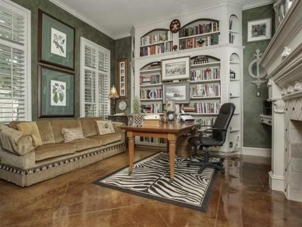 Study with louvered windows, white built-ins, a wooden desk, and a comfy sectional sofa.