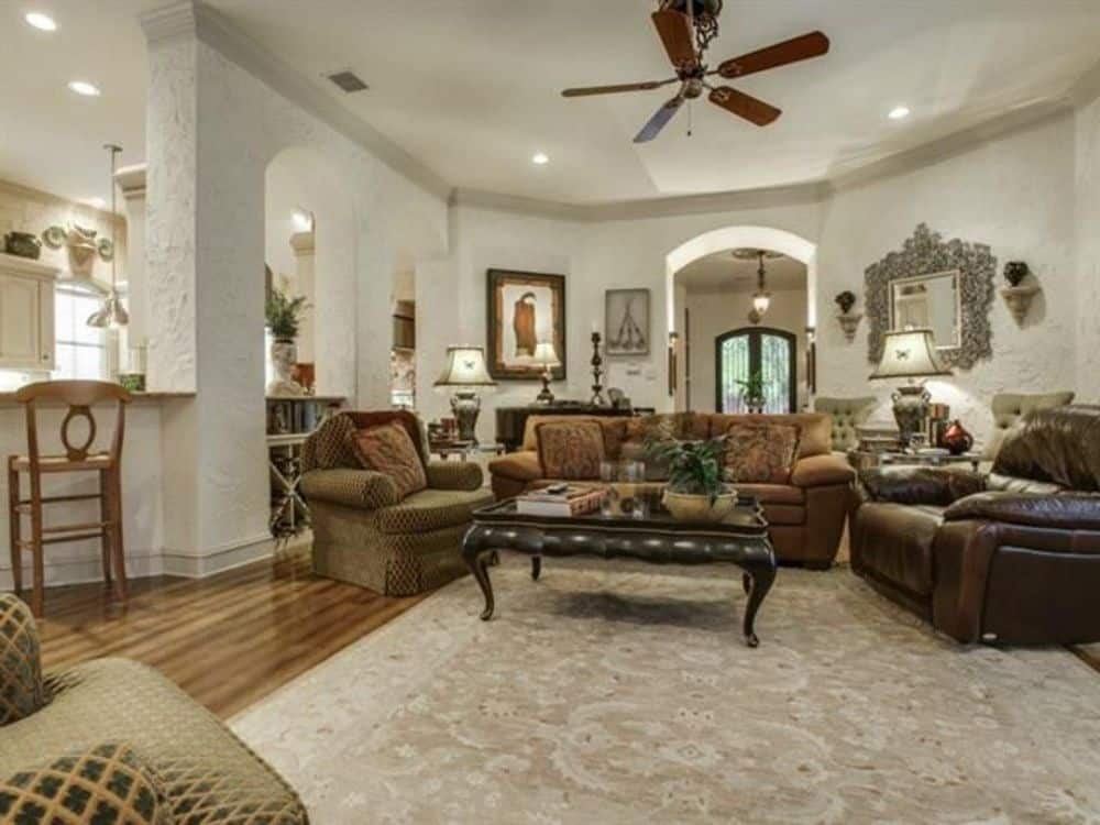 Family room with fabric and leather seats and a wooden coffee table over a vintage area rug.