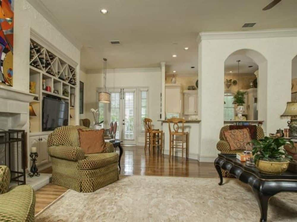The family room includes a TV and white built-ins. It flows seamlessly into the kitchen.