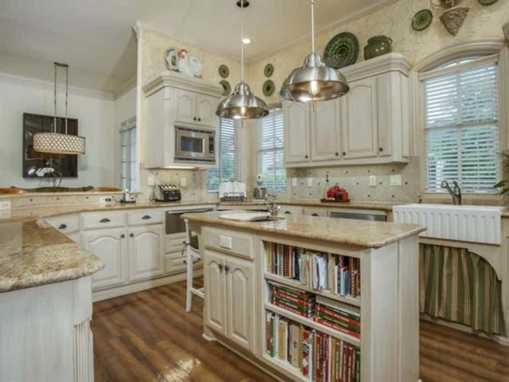 The kitchen offers white cabinetry, granite countertops, a center island, and a farmhouse sink.