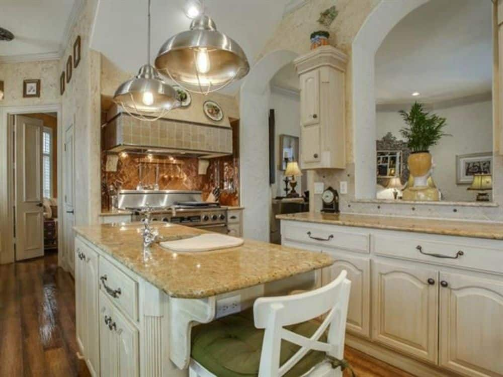 A cushioned counter chair and chrome dome pendants complement the center island.