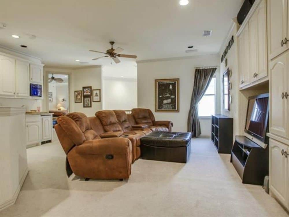 Recreation room with white cabinets, a wet bar, and a leather reclining sofa over the carpet flooring.