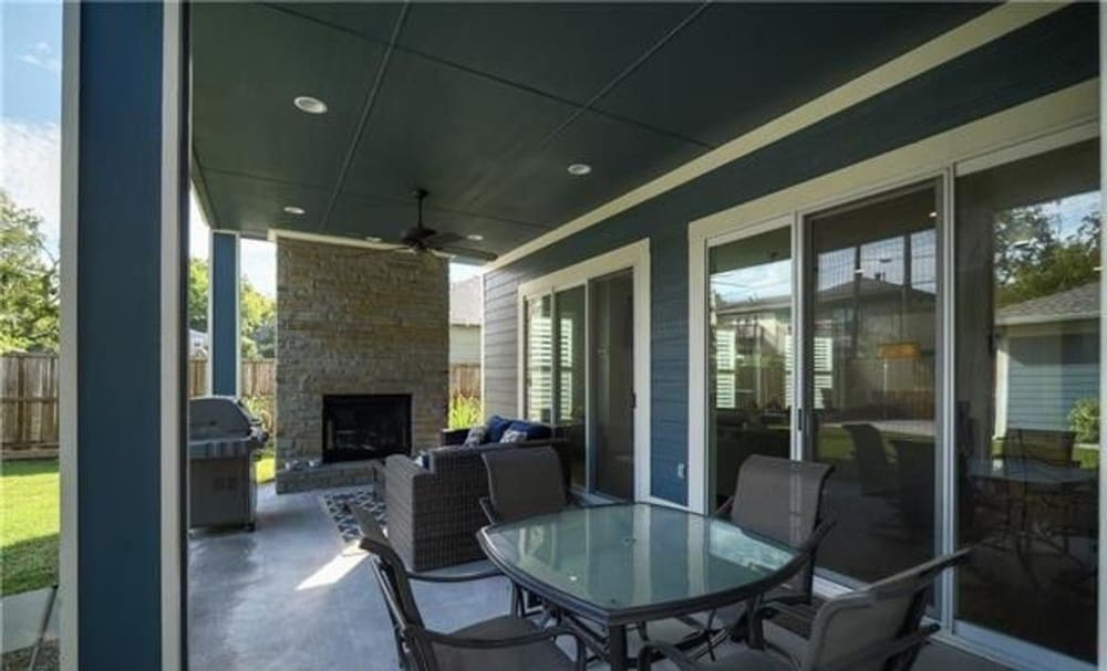 The outdoor living includes a stone fireplace, freestanding grill, and outdoor dining.