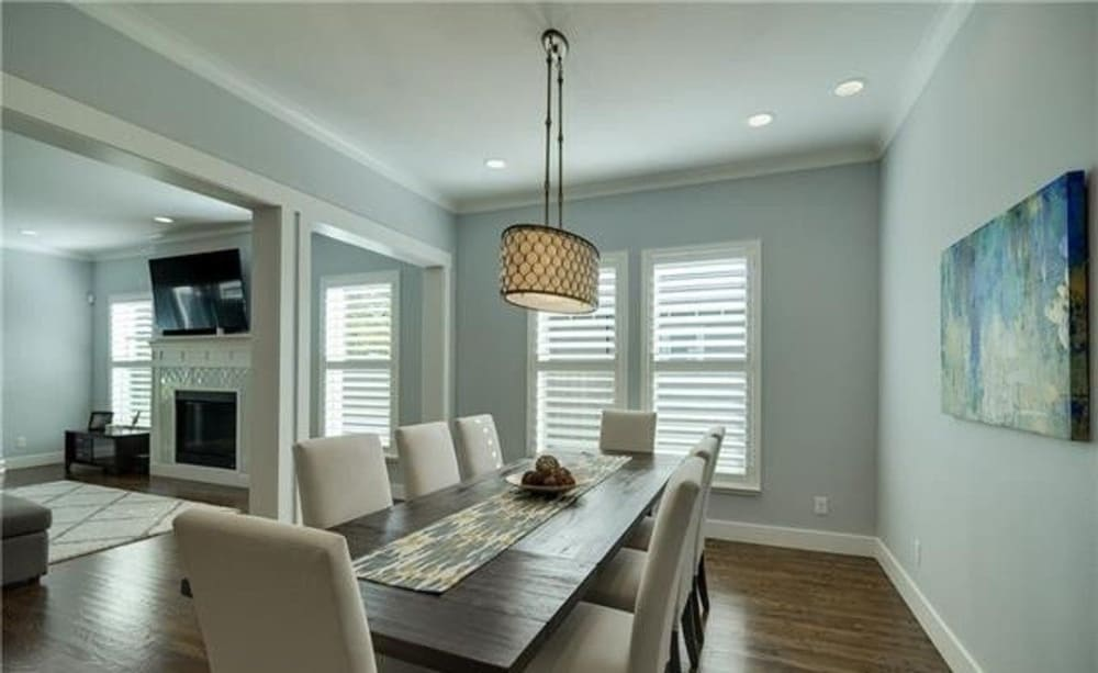 The dining room offers a warm glass pendant, beige upholstered chairs, and a rectangular dining table adorned with a printed runner.