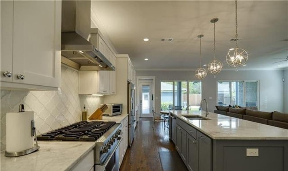 The kitchen island is fitted with gray cabinets, a double bowl sink, and a gooseneck faucet.