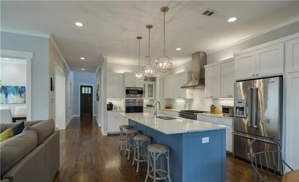 Kitchen with white cabinetry, stainless steel appliances, and a large breakfast island with four seating.