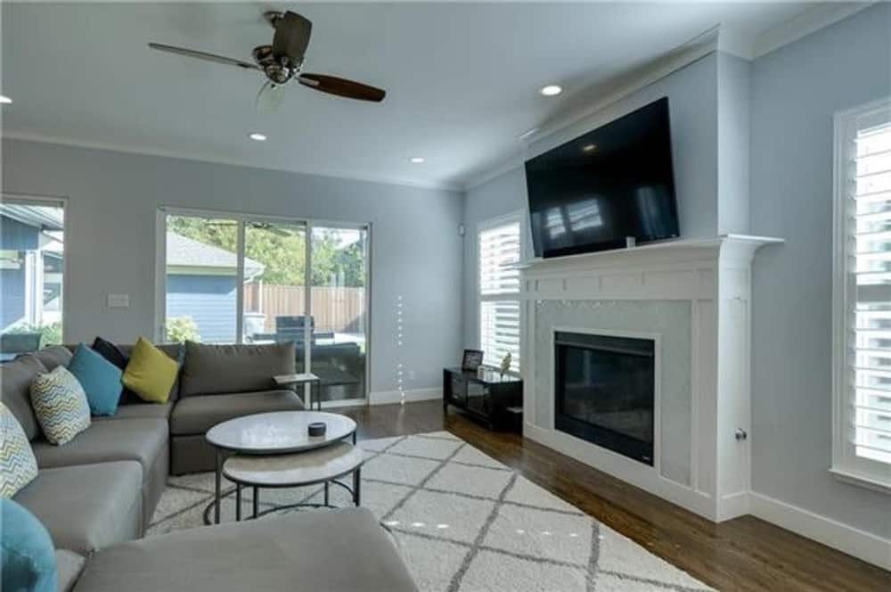 Family room with a gray sectional, round modular coffee table, and a fireplace topped with a large TV.