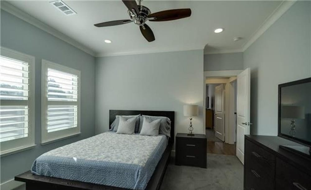 Primary bedroom with dark wood furnishings, carpet flooring, and louvered windows inviting natural light in.