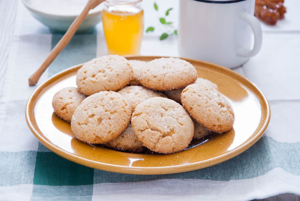 This is a close look at a bunch of honey cookies on a yellow plate.