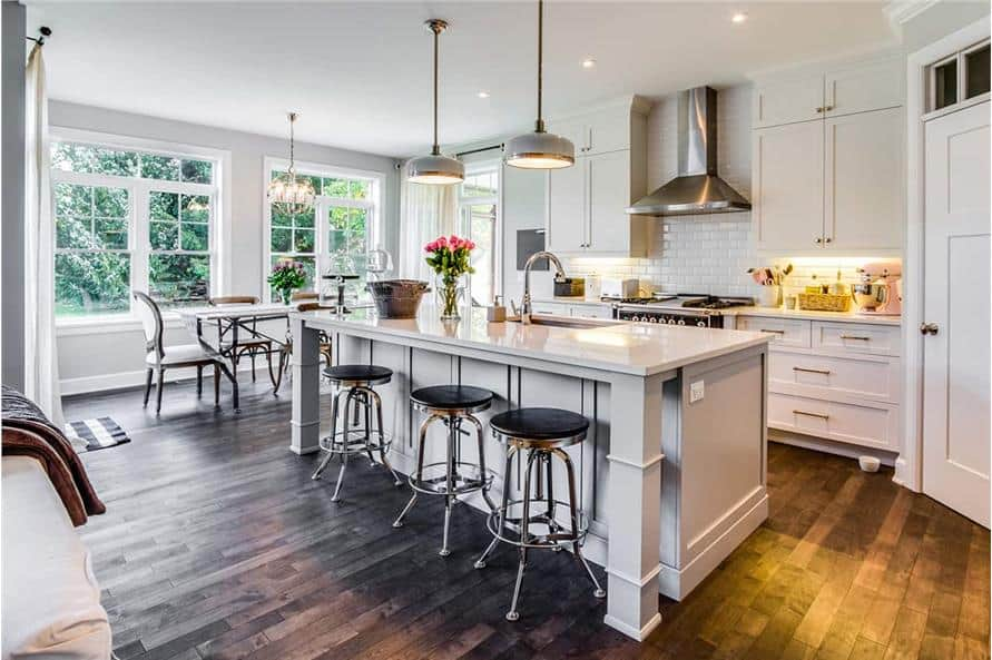 Eat-in kitchen with white cabinetry, subway tile backsplash, breakfast island, and a rectangular dining set.