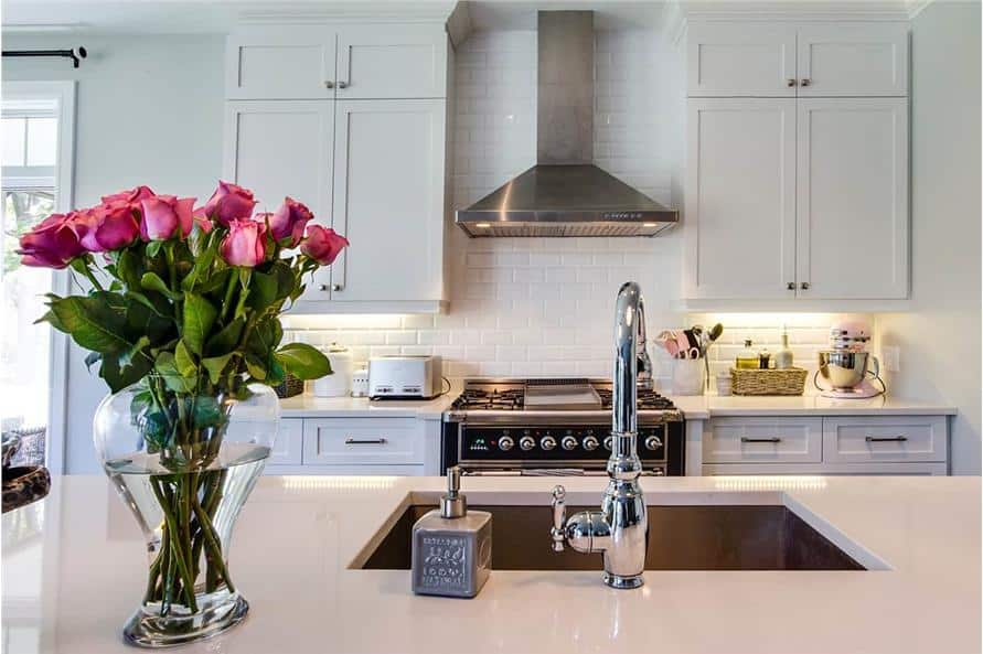 A closer look at the kitchen island fitted with an undermount sink and a gooseneck faucet.