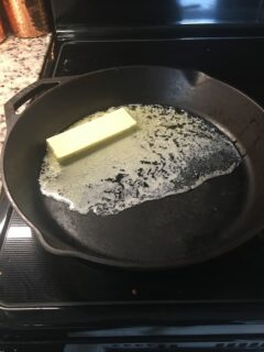 The stick of butter is melted on the skillet.