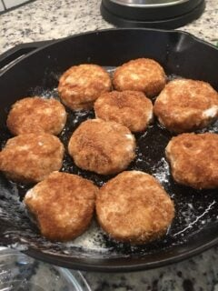 The pieces of biscuit dough are cooked on the skillet.