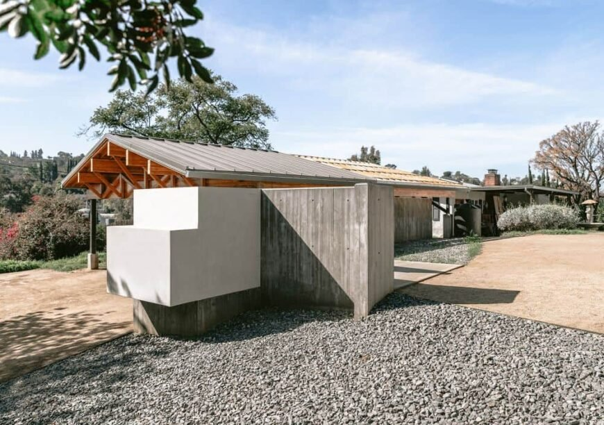 This is a close look at the main entrance of the property with a concrete structure on the side and graveled driveway.