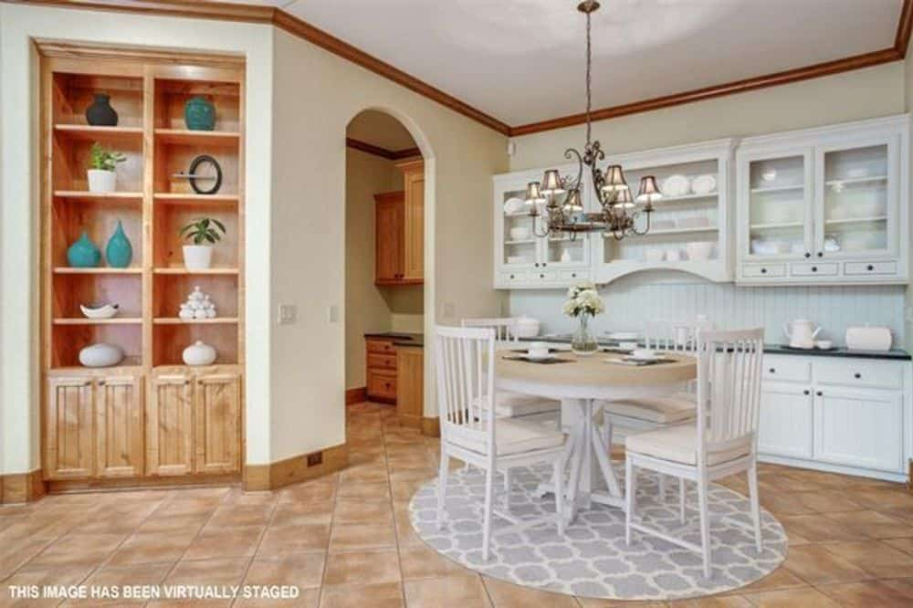 Breakfast nook with glass front cabinets, a buffet bar, and round dining set over a patterned area rug.