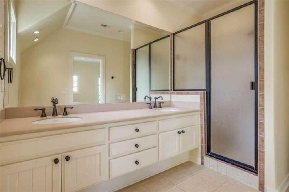 Primary bathroom with dual sink vanity and a walk-in shower enclosed in frosted glass panels.