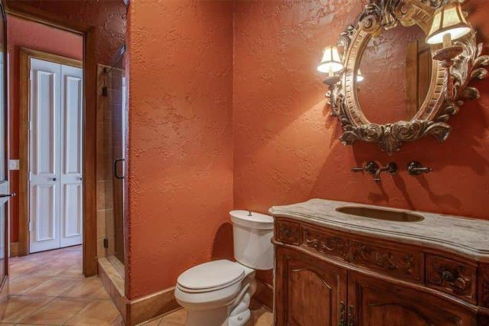 Bathroom with a walk-in shower and a large vanity topped with a vessel sink and wooden cabinets.