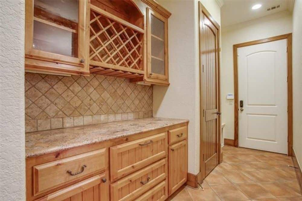 Butlery with natural wood cabinets, a granite countertop, and a built-in wine rack.