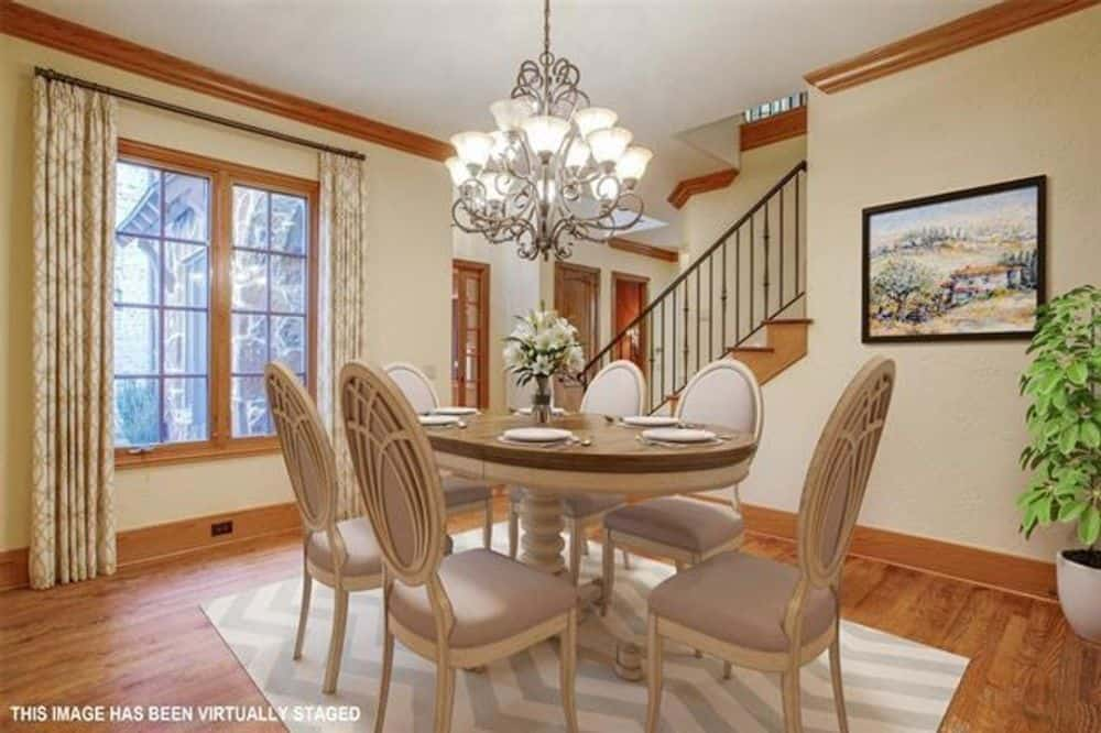 The formal dining room has an ornate chandelier and a 6-seater dining set sitting on a chevron area rug.