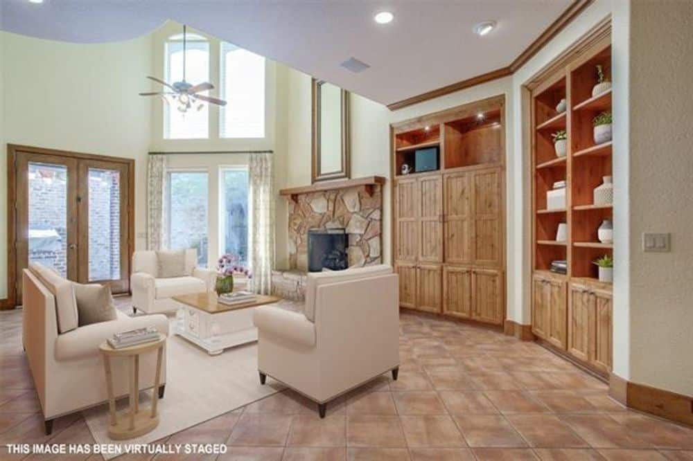 Family room with beige seats, a white coffee table, and a stone fireplace topped with a full-length mirror.