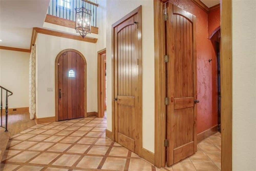 Foyer with an arched entry door and a towering ceiling mounted with a wrought iron pendant.