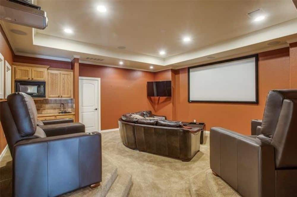 Recreation room with leather seat, projector screen, and a wet bar.