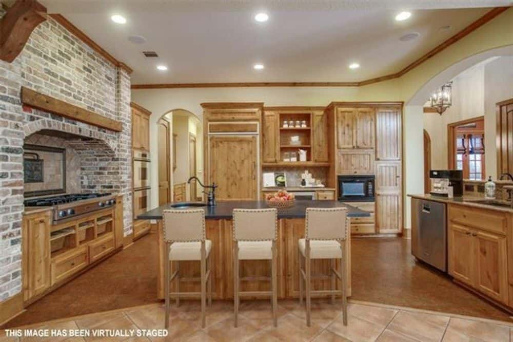 The kitchen offers wooden cabinetry, a cooking alcove, and a center island paired with cushioned counter chairs.