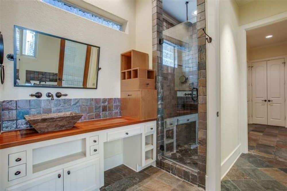 This bathroom has limestone flooring and red textured walls adorned with a carved wood mirror.