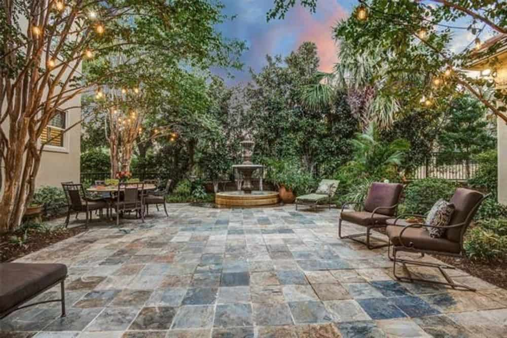 An open patio filled with cushioned chairs, a round outdoor dining, and a stunning fountain.