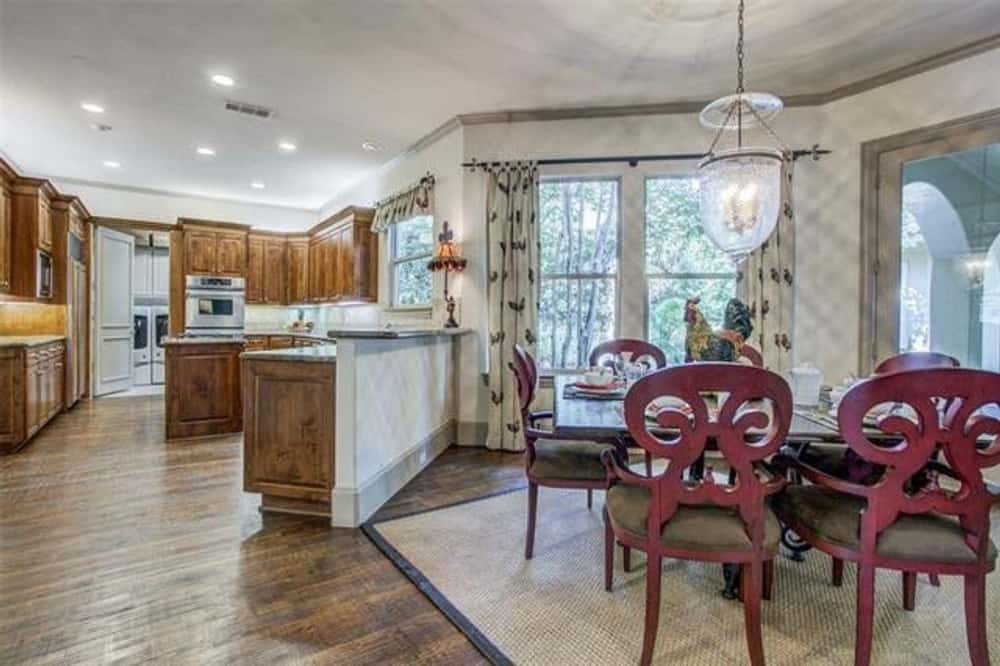 Eat-in kitchen equipped with wooden cabinetry, stainless steel appliances, a raised eating bar, and a wooden dining set.